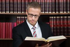 Young male lawyer reading legal book at courtroom Kuvituskuvat