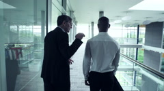 Two Business men talking while walking in office corridor - stock footage