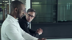 Business men having a discussion in office corridor Stock Footage