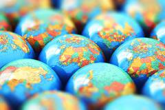 Small Earth globes with world maps - stock illustration