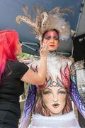 Artist Applies Colorful Body Paint To Female Model At Festival Stock Photos