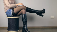 Girl sitting on the pouf take off one's shoes, and shows class Stock Footage