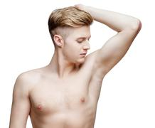 Handsome young man sniffing his armpit - stock photo
