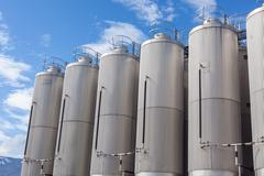 Giant industrial tanks on the bright blue sky Stock Photos