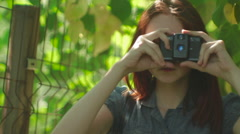 Paparazzi Girl Makes Photo in the Garden with Green Trees Close-Up Stock Footage