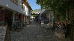 Two men walking on a street near souvenir shops in Mostar - stock footage