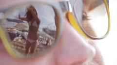 The girl in the reflection of sunglasses is dancing and waving his arms Stock Footage