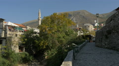 View of people walking on a paved street near the river in Mostar Stock Footage