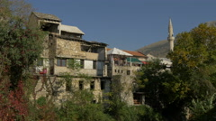 View of stone buildings and a minaret in Mostar Stock Footage