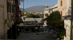 Two men carrying a ladder near an outdoor restaurant in Mostar Stock Footage