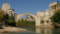 Tourists on Stari Most and people walking on the shore of the river in Mostar Stock Footage