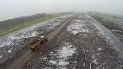Aerial bird view of tractor with trailer moving dirt sand over a snowy road 4k - stock footage