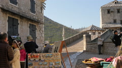 View of Asian tourists near souvenir stalls and Stari Most in Mostar Stock Footage