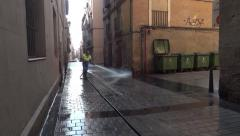 Man washes a street paved with stone cube with water using a hose Stock Footage