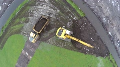 Aerial top down ascending hydraulic excavator loading mud sand in dump truck 4k Stock Footage