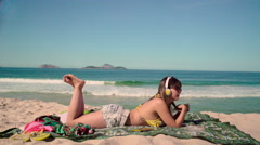 Sexy woman relaxing on beach and listening to music Stock Footage