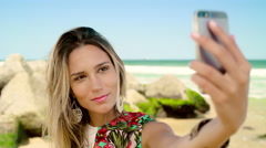 Attractive woman taking a selfie on smartphone at Ipanema beach - stock footage