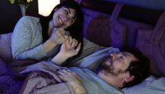 Couple in love at night in bed making peace after fight falling asleep Stock Footage