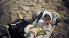 1979: Baby in carrier falling asleep sucking thumb on beach sand. Stock Footage