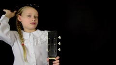 girl measures the hat and holding a guitar in a white dress on a black - stock footage