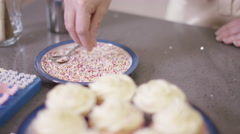 4K Close up of hand sprinkling topping onto fresh cupcakes Stock Footage