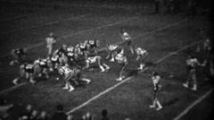 1978: High school football night game quarterback option running play. Stock Footage