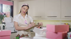 4K Woman with home bake business preparing deliveries & taking orders over phone - stock footage