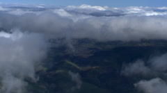 Flight past cloud puffs over rugged terrain, passenger POV Stock Footage
