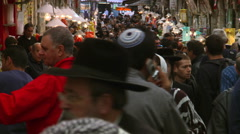 Crowded narrow marketplace in Jerusalem, people passing close to camera - stock footage
