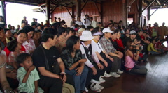 Crowd of spectators watching dancers in an open pavilion in Cambodia Stock Footage