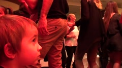 Child watches dancing people - stock footage