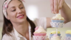 4K Smiling woman with bakery business putting finishing touches onto cupcakes - stock footage