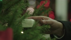 Close up shot of man's hand taking ring box out of Christmas tree and opening it Stock Footage