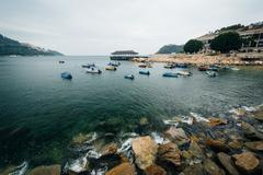 Rocky coast and boats at Stanley, on Hong Kong Island, Hong Kong. Stock Photos