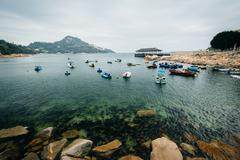 Rocky coast and boats at Stanley, on Hong Kong Island, Hong Kong. - stock photo