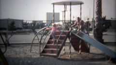 1979: Dad and son go down metal playground slide in tandem. Stock Footage