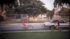 1979: Kids fake bike skateboard crash on city sidewalk. - stock footage