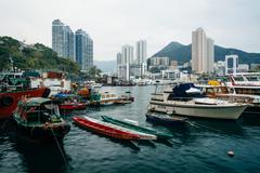 Boats docked at Ap Lei Chau and view of skyscrapers and mountains in Hong Kon Stock Photos