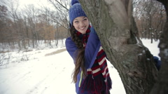 Portrait of a young girl hidding behind a tree trunk Stock Footage