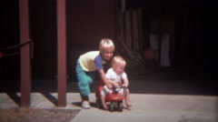 1979: Blonde brother pushing baby sister in kids vehicle. Stock Footage