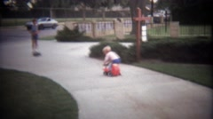 1979: Blonde young boy pedals play toy scooter around sidewalk. Stock Footage