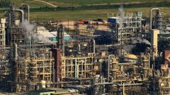 Flight past oil refinery smokestacks Stock Footage