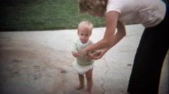 Stock Video Footage of 1979: Caucasian blonde toddler pulling school bus toy on sidewalk.