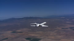 Air-to-air rear view of jet flying over desert Stock Footage