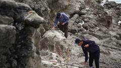 Men prepare fishing rod line, strong waves, Atlantic ocean cliff, Portugal - stock footage