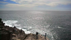 Men fishing off Atlantic ocean cliffs, long shot, blue sky, Portugal Stock Footage
