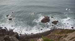 Pan left on view from high cliff down to Atlantic ocean rocks and waves - stock footage