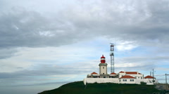 Red lighthouse at Cape Cabo da Roca, pan left to tourists, Portugal Stock Footage