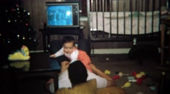1971: Baby crawls on dad while watching tv laying on floor. Stock Footage