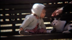 1971: Toddler girl sitting on park bench playing with cat. Stock Footage